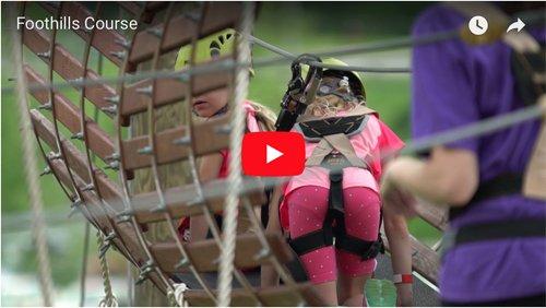 Little girl climbing through barrels hanging in the sky