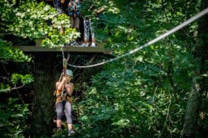 Girl zipping through trees in Summer Blowing Rock Boone