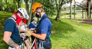 Employee Helping Guests get ready for adventure park