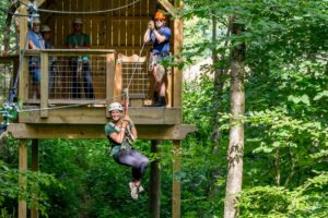 Woman zipping from treehouse in summer
