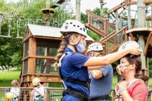 employee helping child get ready for adventure course