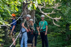 Smiling guests on zip line tree platform in summer